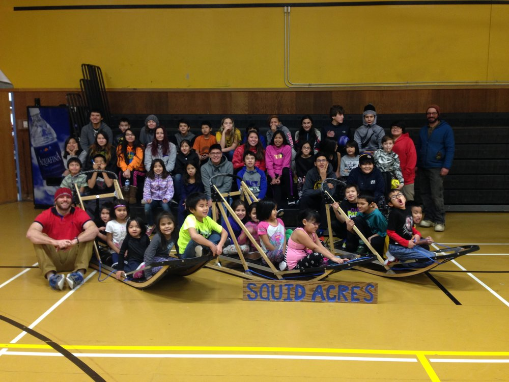 Students posing with the three sleds they built.