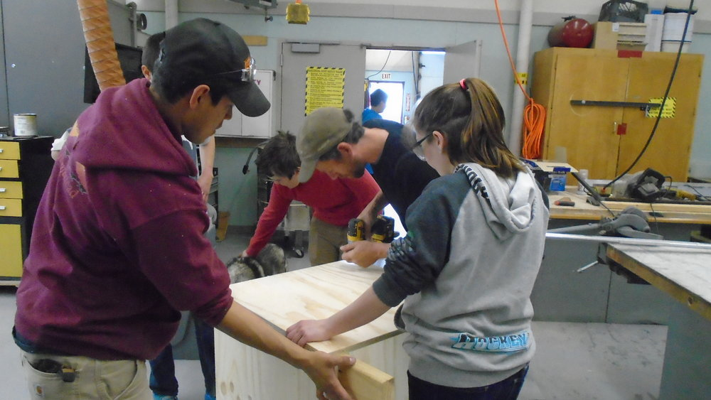 Students buidl dog house in shop with Jessie Holmes and Joe Bifelt.