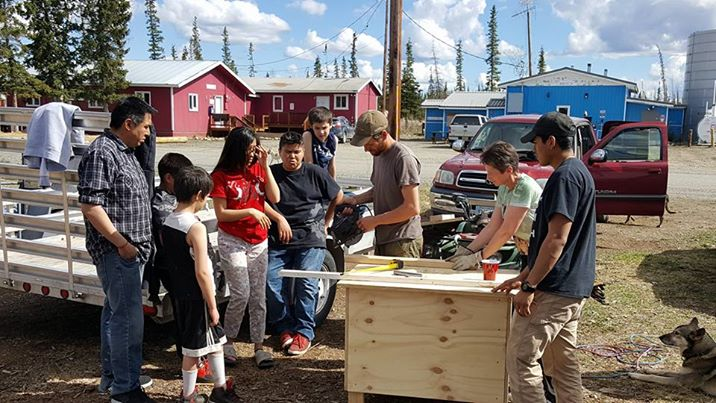 Students build dog house outside with Jessie Holmes and Joe Bifelt.