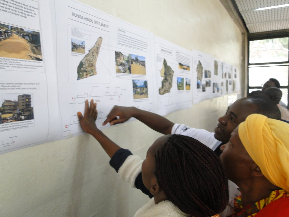 Members of five settlements in Kitui Town interact with data they collected during the Kitui Studio data collection process at the University of Nairobi.