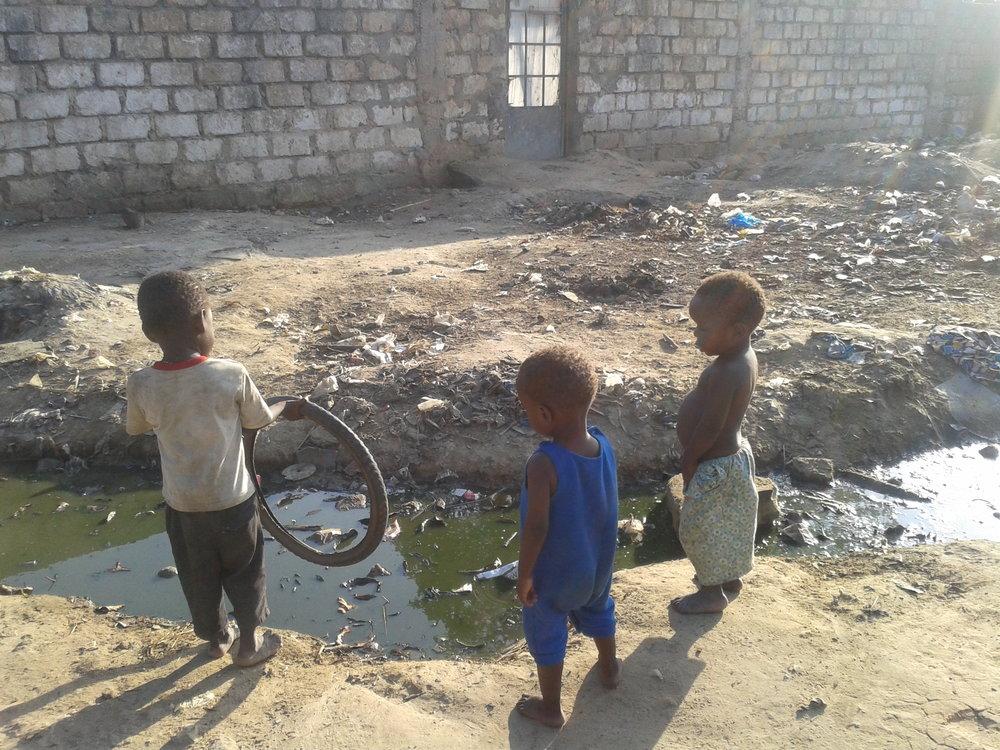 Children playing near an open raw sewer