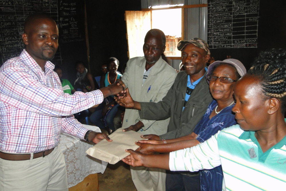Mr. Karrisa hands over the Kiandutu Profile report to the Kiandutu settlement leadership