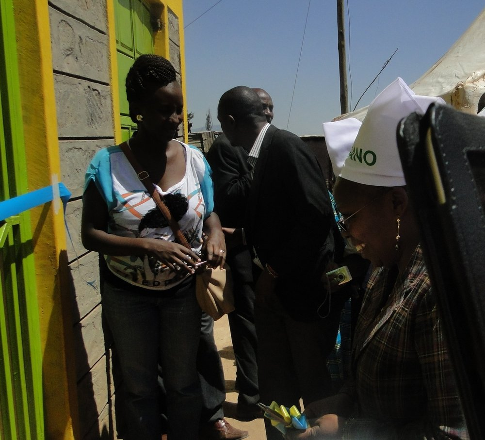 Minister Esther W Njuguna cuts the tape to officially open the Molo Sanitation block