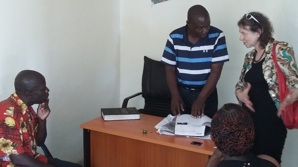 Standing: Chair of the Complaints and grievance Committee, Mr. Onyango takes through Jane Katz of Habitat through the beneficiary documentation. Sited is Wilberforce Onyango, a resident of Kibera
