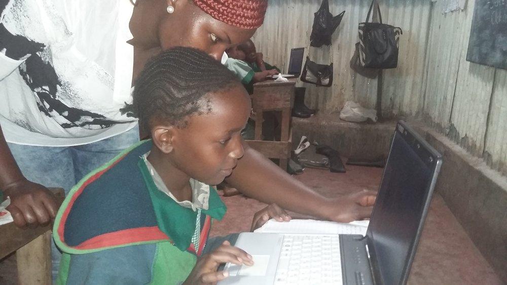 Janet Moraa a pupil at Church on the Rock receives instructions from Tr. Kate of Muungano wa Wanavijiji.
