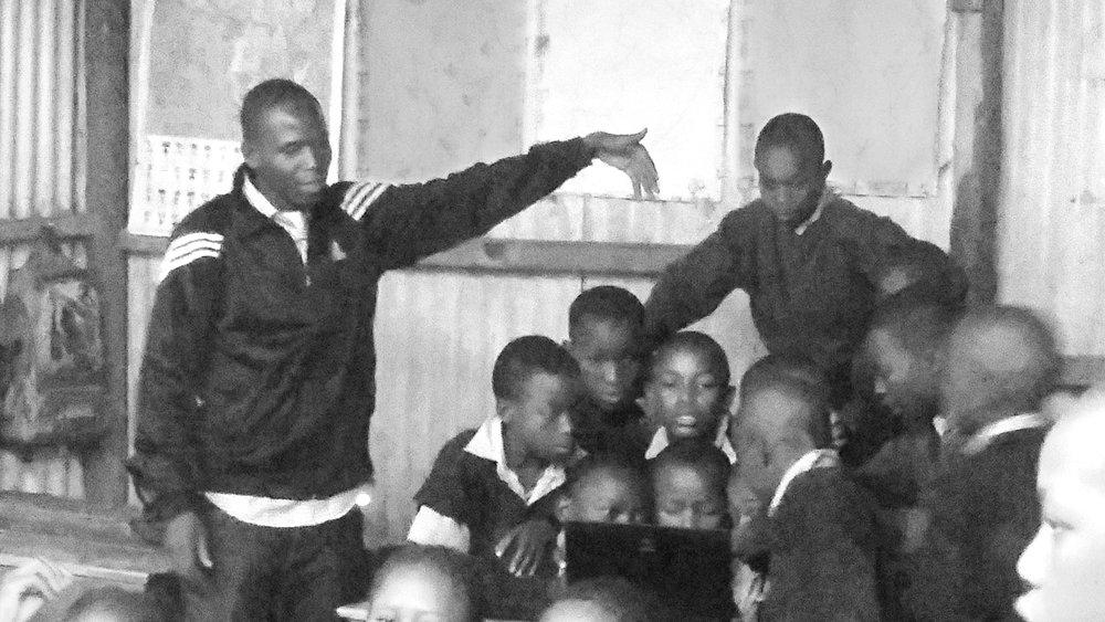 Tr. Evans Otibine of Akiba Mashinani Trust moderates the computer lesson.