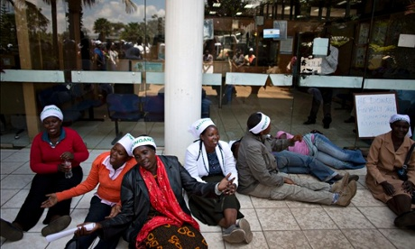 Mukuru slum women barricade the entrance to the health ministry. The writing on their headbands reads 'togetherness' in Swahili.Photograph: Karel Prinsloo/Guardian