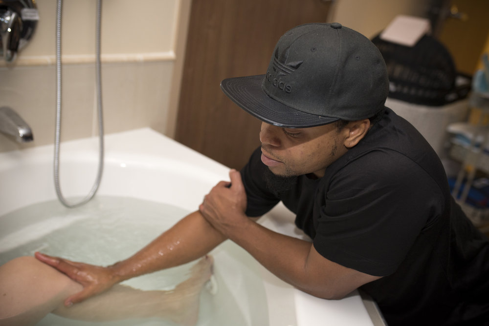 A loving father rests his hand on his wife and encourages her in her water birth at the UF Birth Center.