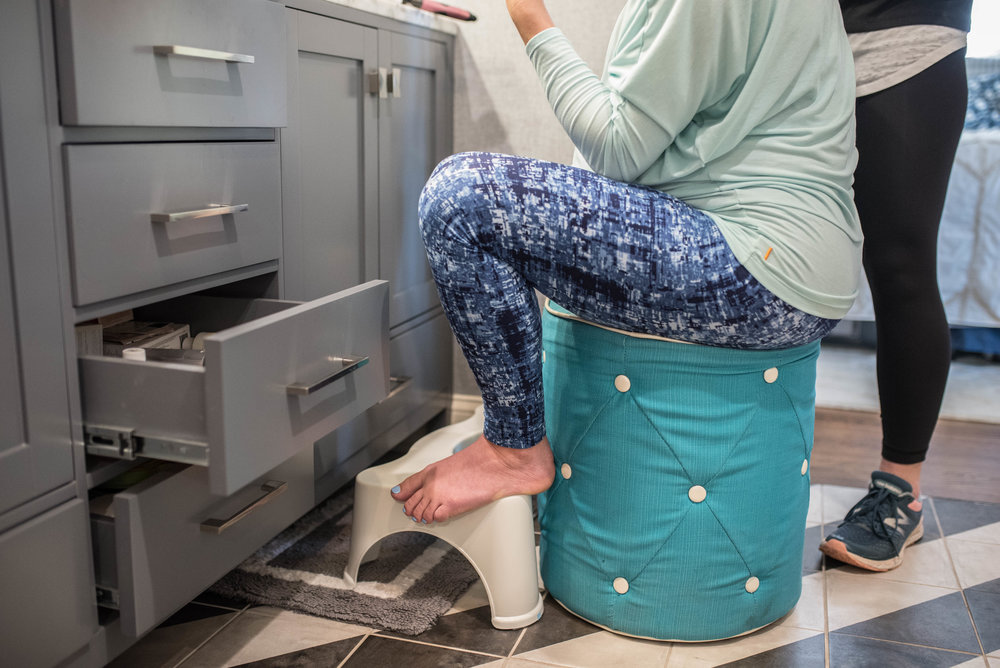 Laboring mother squatting on a Squatty Potty during early labor at home in Jacksonville.