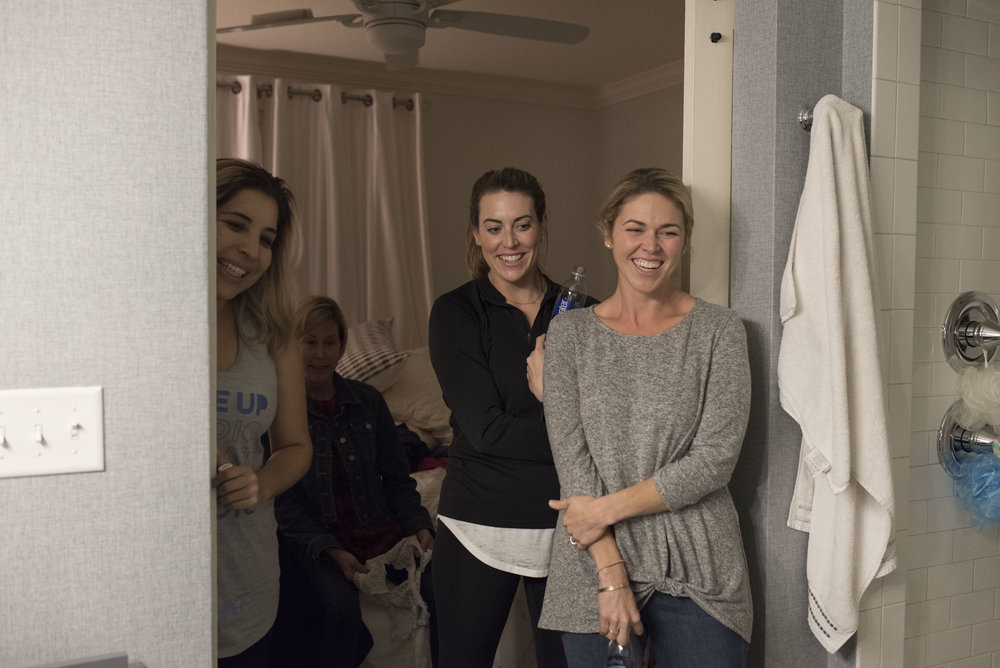 Sisters, doula, and mom laugh with laboring mom while she is getting ready to head to the hospital.