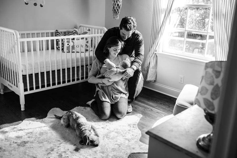 A young couple holds their first newborn baby in front of the crib in their home. Their dog lays on the floor next to them.