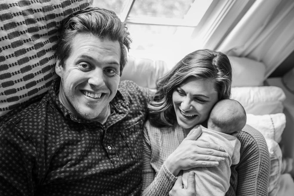 Mom and dad laugh at the photographer while holding their newborn baby.