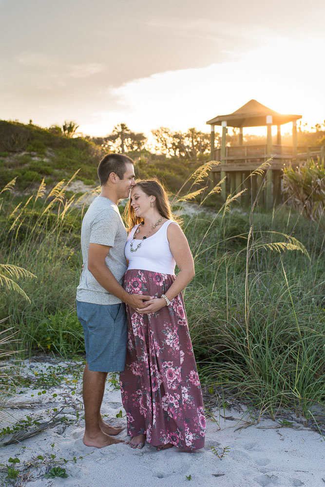 First time parents snuggle up on the beach for a session with their Jacksonville maternity photographer, Dallas Arthur.