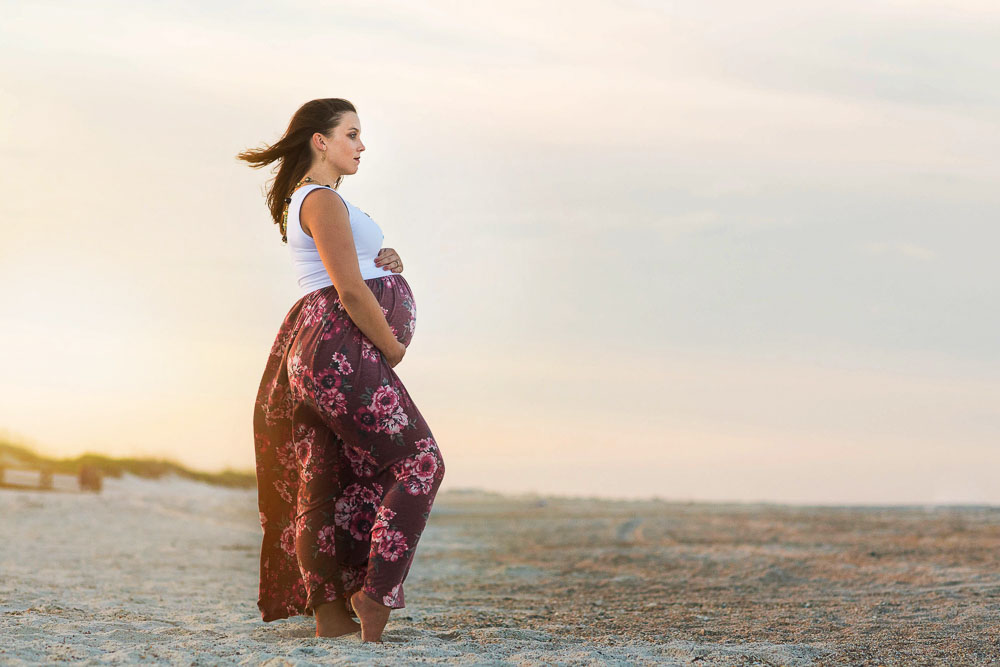 A pregnant mom poses for her maternity photo session at a beach in Jacksonville, Florida. She is pregnant with her first baby.