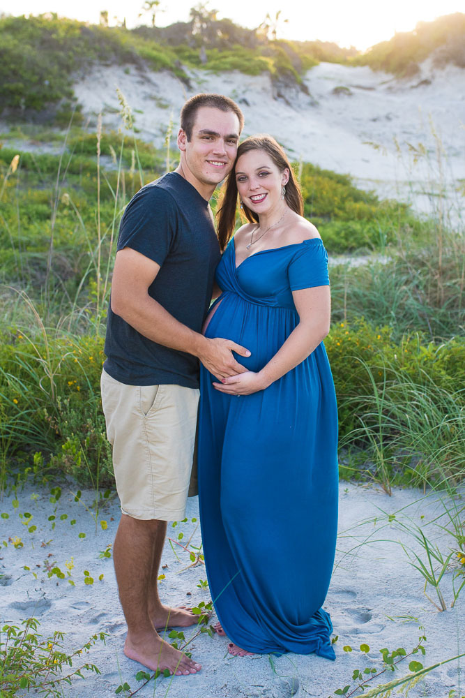 A young couple smiles at the camera during their pregnancy photography session at a beach in Jacksonville.