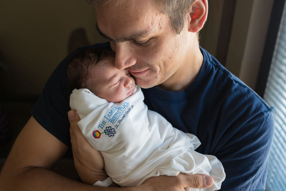 """A new dad snuggles his newborn daughter. She is swaddled in a hospital swaddle that says """"The Family Birth Place, St. Vincent's Healthcare."""""""