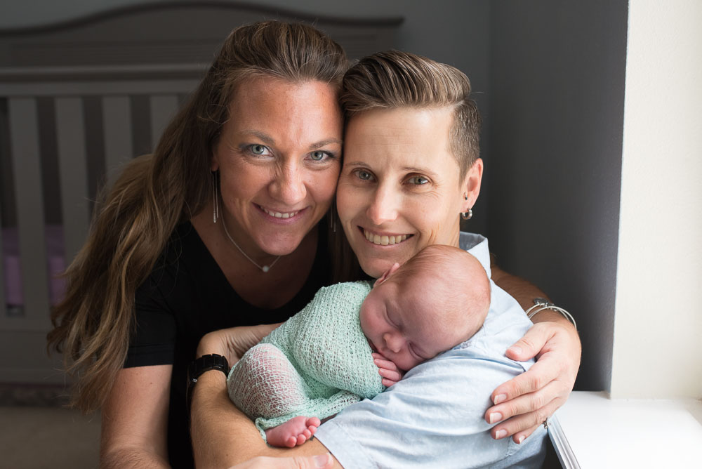 Homosexual couple looks at the camera during their in home newborn session in Jacksonville with their beautiful little girl.