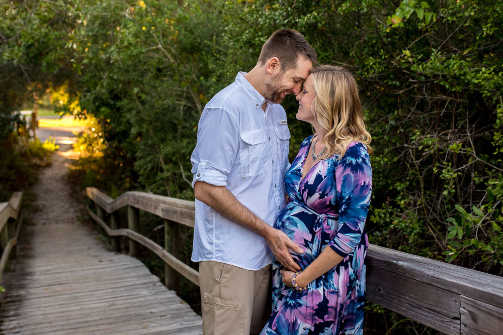 Expecting couple snuggles on the boardwalk during a maternity photo session with photographer Dallas Arthur.
