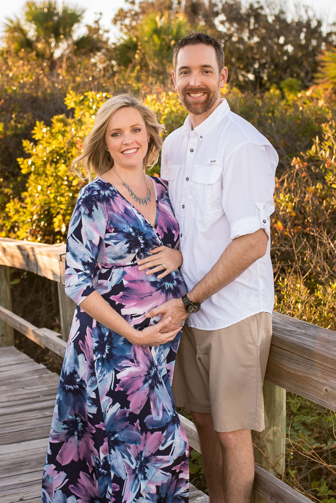 A happy couple smiles at the camera on a boardwalk during their maternity photo shoot.