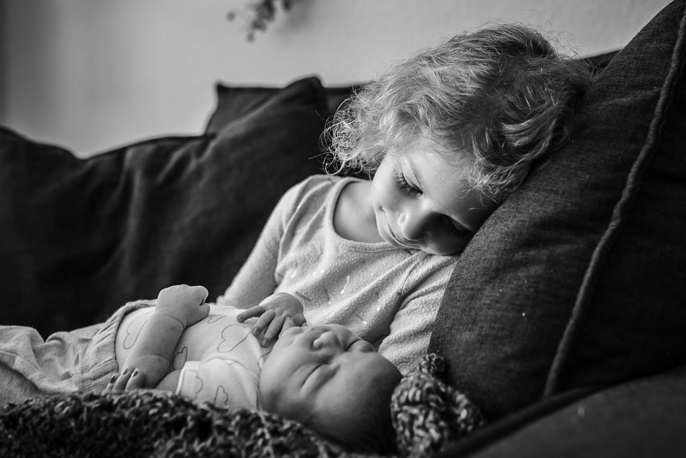 Big sister looks lovingly at her newest baby brother. Both babies were born at home with a midwife.
