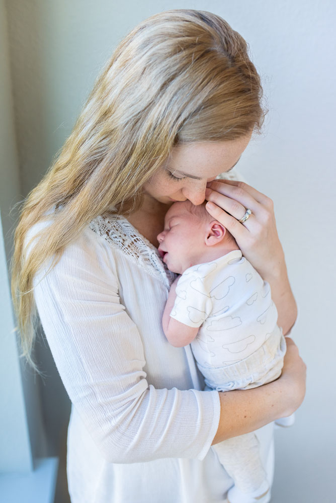 A beautiful mama holds her baby boy close for a snuggle during their Fresh 48 or Just Born photo session.