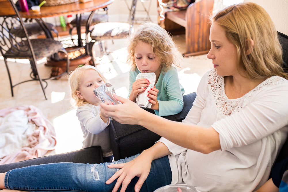 Real life images of a mom giving juice boxes to her toddlers while sitting with her newborn baby.
