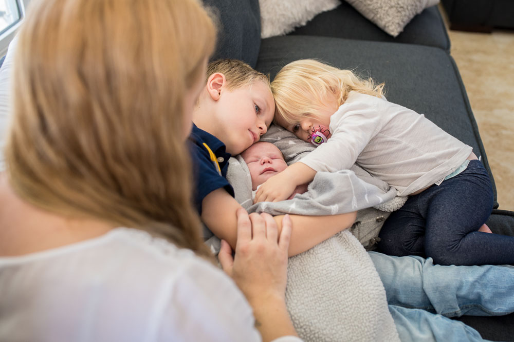 Big brother and sister rest on the sofa, cuddling their baby brother, Jack.