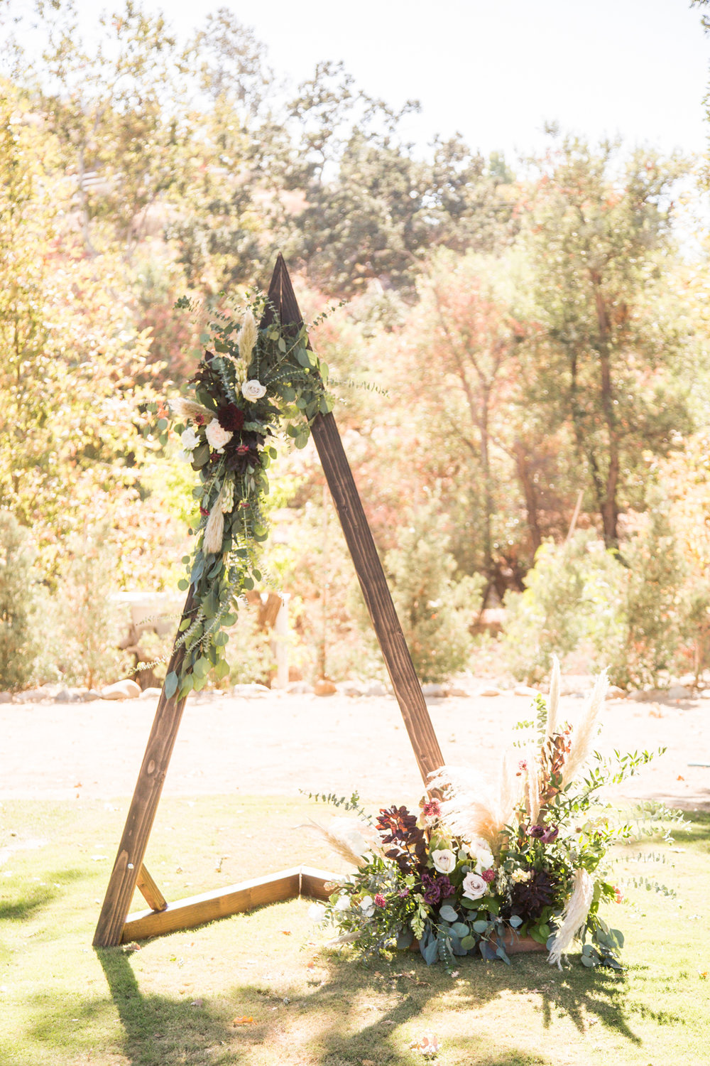 Wooden Triangle Arch adorned with moody florals