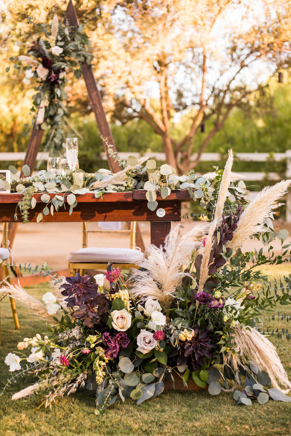 Fall themed sweetheart table florals with pampas grass
