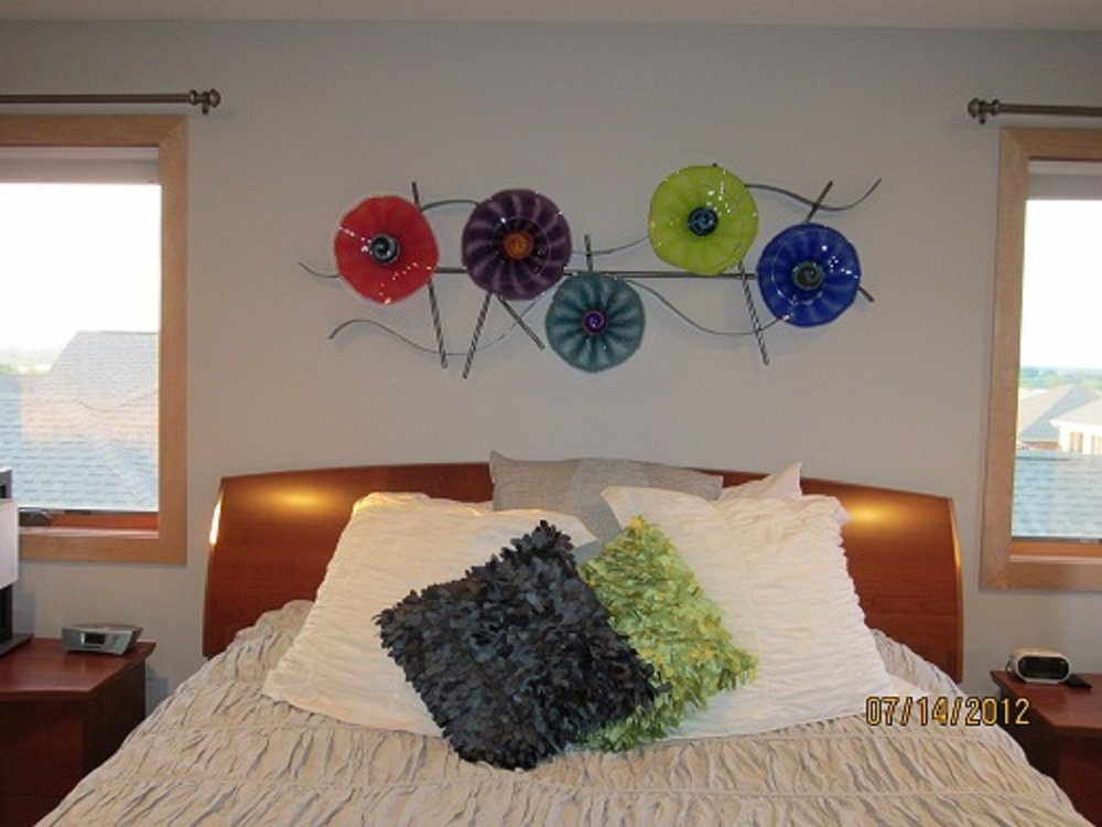 Highlighting all the colors in the master bedroom this trellis sculpture of metal and glass makes the room shine my flowers hang with or without the metal and come in a variety of sizes and color. shown over this bed this glass piece completes the room.