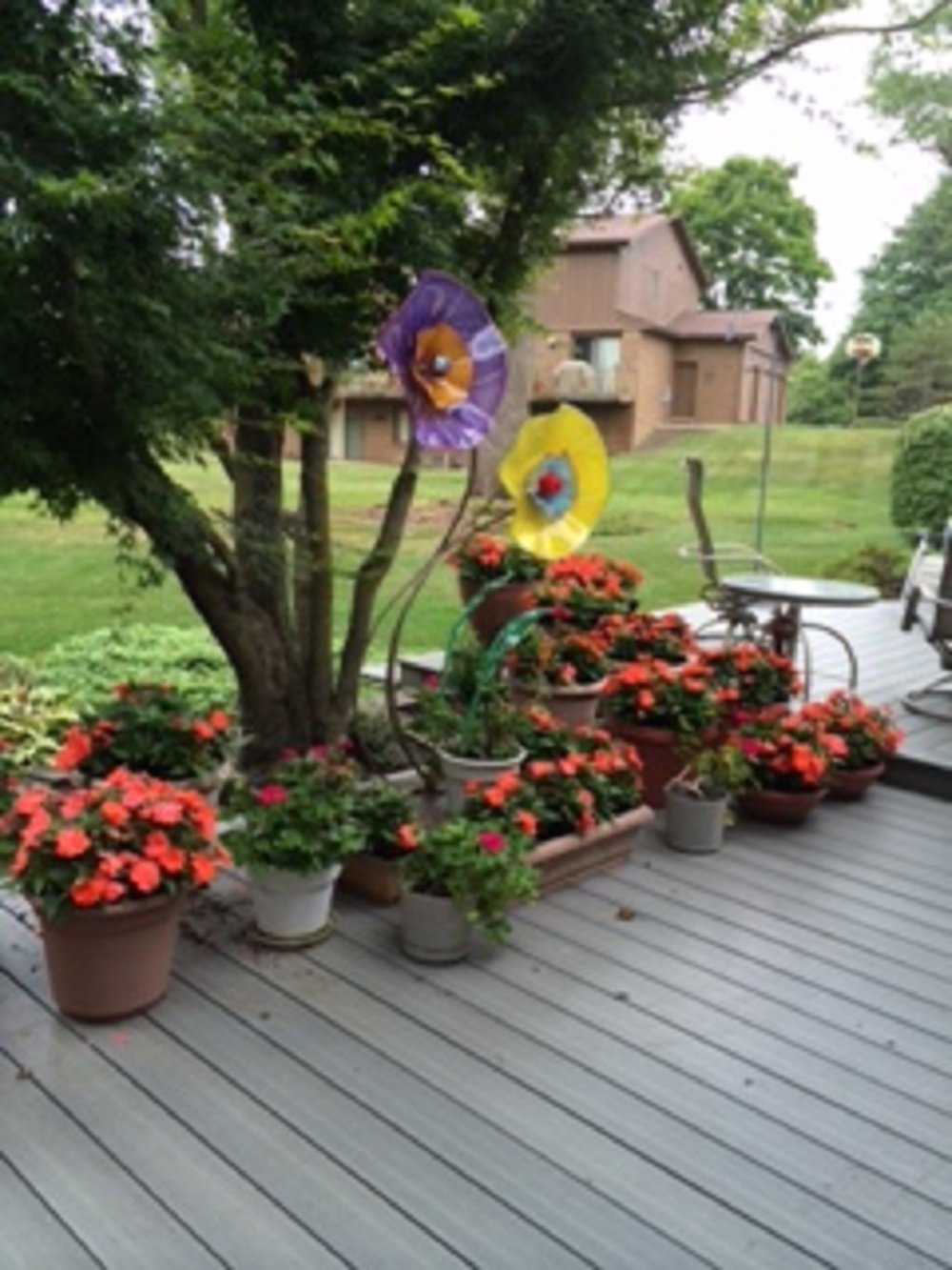 Look out your window and see these flowers that bloom all year long located in this flower garden the pieces shown are @18″ colors are purple with amber and yellow with teal the sculpture stands 69″.