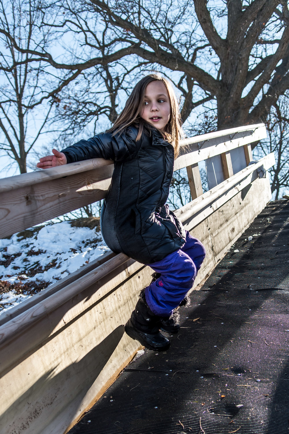 Paige Bemau, 8, slides down the railing of the ramp leading onto the frozen water of Echo Lake Saturday afternoon during Burlington's Hot Chocolatefest.