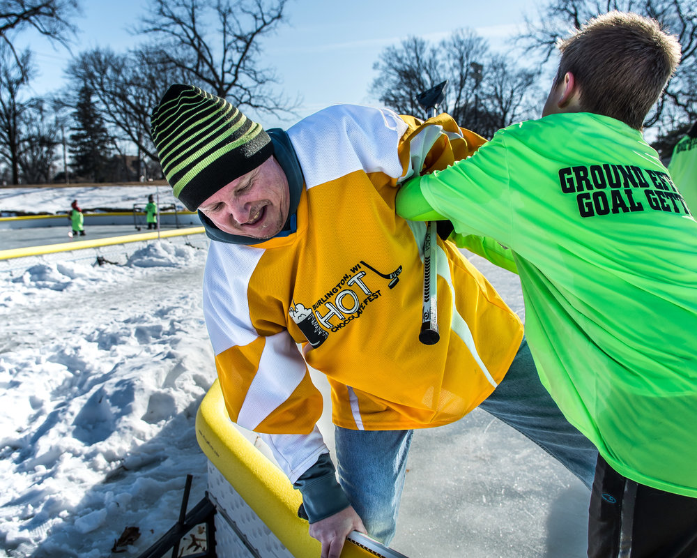 Ben Van Lysal attempts to shove his dad Jeff out of the ring during an adults versus kids game of Broom Ball on Echo Lake during Burlington's Hot Chocolatefest Saturday afternoon.