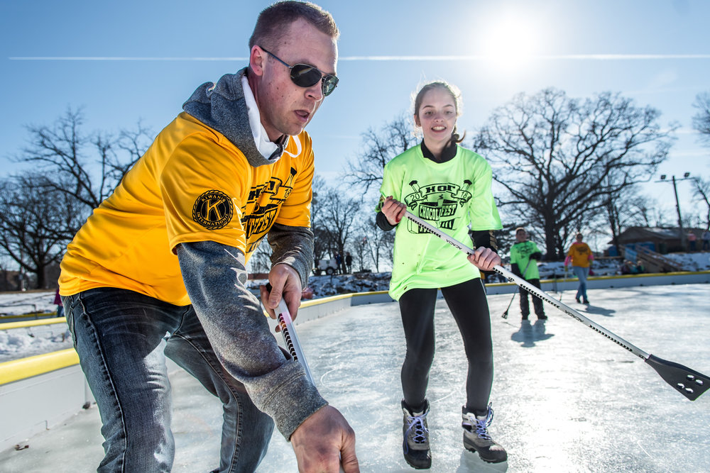 Levi Katelsen, Burlington, runs for the ball closely followed by Cheyenne Cole, 14, during an adults versus kids game of Broom Ball on Echo Lake during Burlington's Hot Chocolatefest Saturday afternoon.