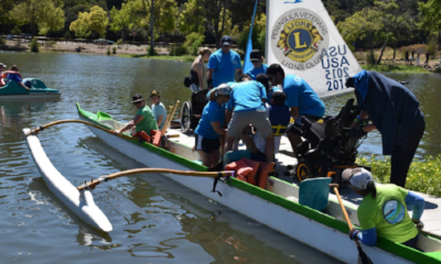 The outrigger canoe is being loaded with several disabled participants.