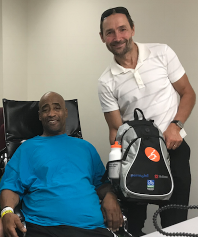 Kevin, who suffered an SCI in July, receiving a Care Package which included a Google Home Mini and a specialized Fleximug allowing hands-free drinking and Peets Coffee Vouchers.