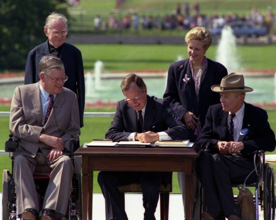 In one of the most iconic moments for the disability community, President George Bush signs into law the Americans with Disabilities Act of 1990 on the South Lawn of the White House.
