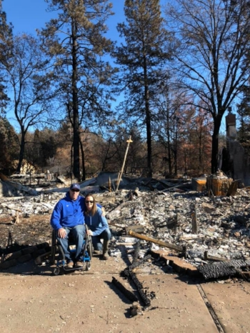 Paraplegic and Paradise resident, Mike Clement, along with his wife, Jen, in front of what was once their home.
