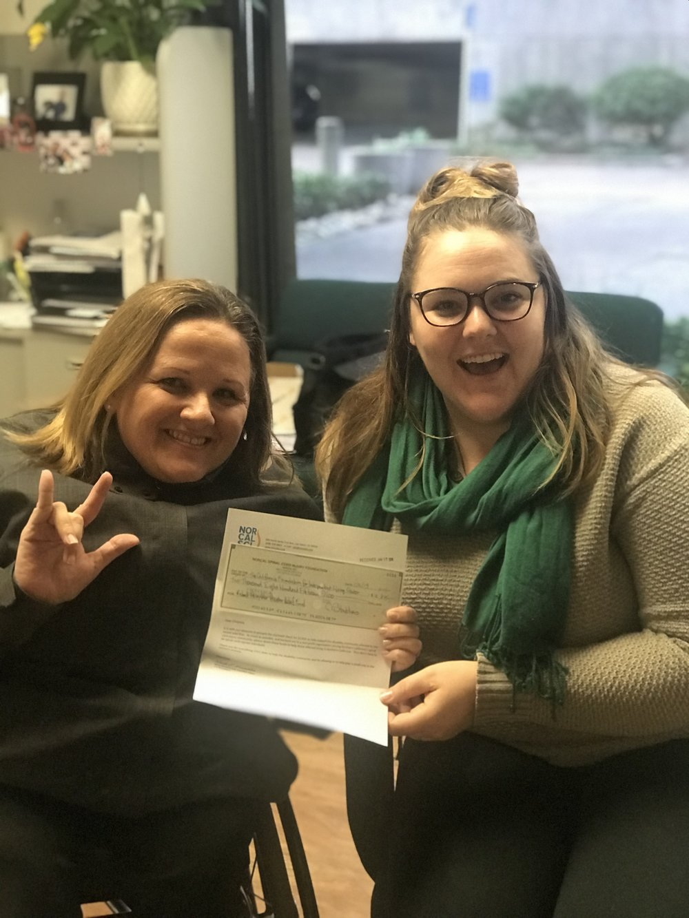 On the left, Christina Mills, CFILC's Executive Director, holds NorCal SCI's check along with CFILC's Ability Tools Program Coordinator, Emily Flynn.