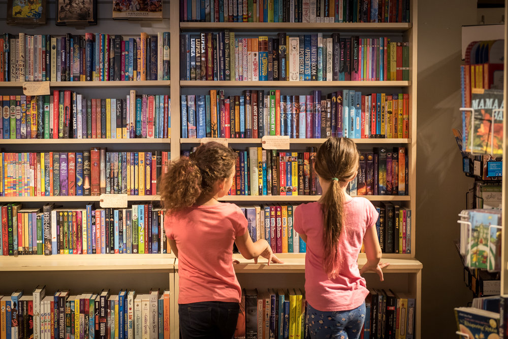 Social Media Photography taken for Independent Book Store Day 2017 - Astoria Bookshop, NYC. Two young girls in pink shirts stare at a bookshelf filled with colorful children's books.