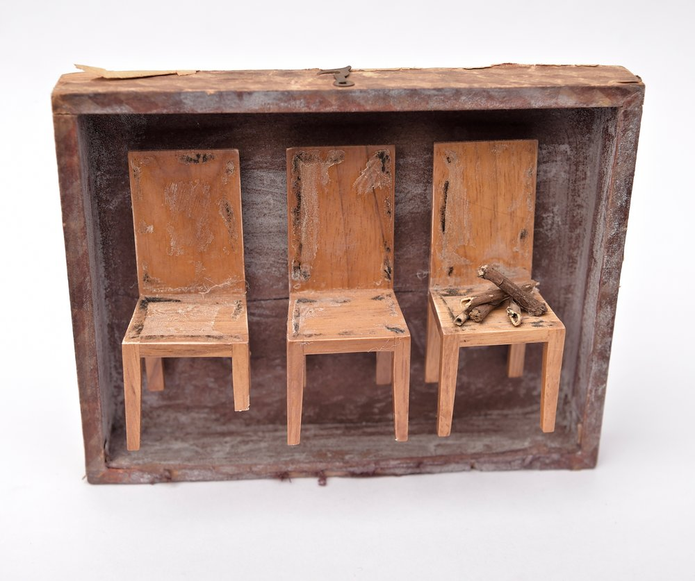 old shallow wooden tray with 3 small found dolls chairs in a row all with differing brokwn parts, e.g. legs not long enough