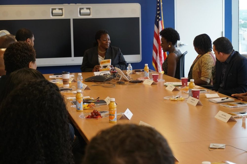 Wilglory speaks to a room filled with representatives from DC's college access organizations at a book breakfast organized by former DC Chancellor, Kaya Henderson (sitting at the head of the table).