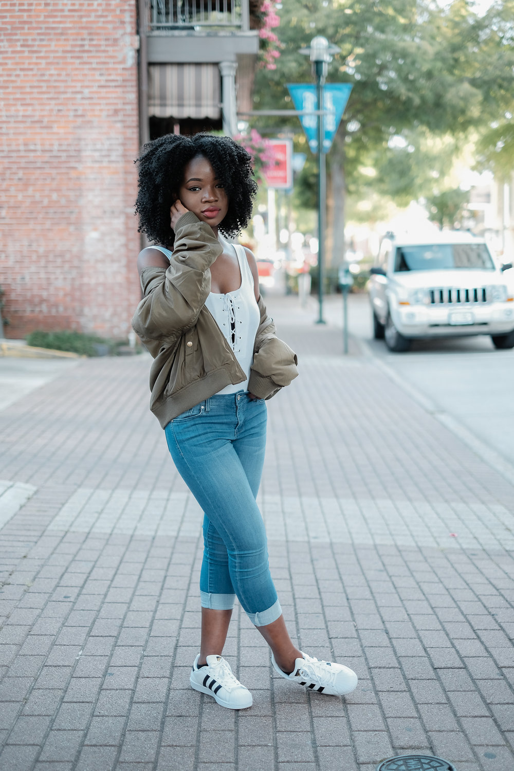 black girl in blue jeans and white top