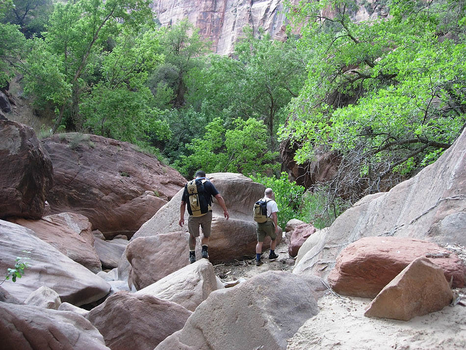 The Exit - Descend the canyon. The floor of the canyon is littered with large blocks and the walk out is strenuous. Very difficult in the dark. Take it slow and have fun. Work your way down the streambed, following signs of traffic. It takes one to two hours, plus time for playing in pools. The masonry wall of the 2nd switchback is clearly visible from the canyon bottom just before the largest and best swimming hole. Find a trail in the woods from the level of the pool leading to the road.Emergency (NOT alternative) Exit: It is possible to follow a traversing trail across to the end of the top switchback of the Pine Creek road. The trail is closed except for emergencies, REAL emergencies. This trail is eroded and collapsed in a couple of spots and is easily seen from the Canyon Overlook trail as it has a huge impact on the sandy hillside. Following the drainage is the low impact exit—please use it.