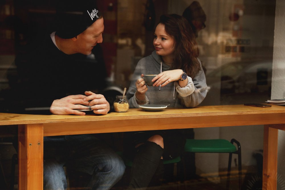 couple sat in the window of coffee shop