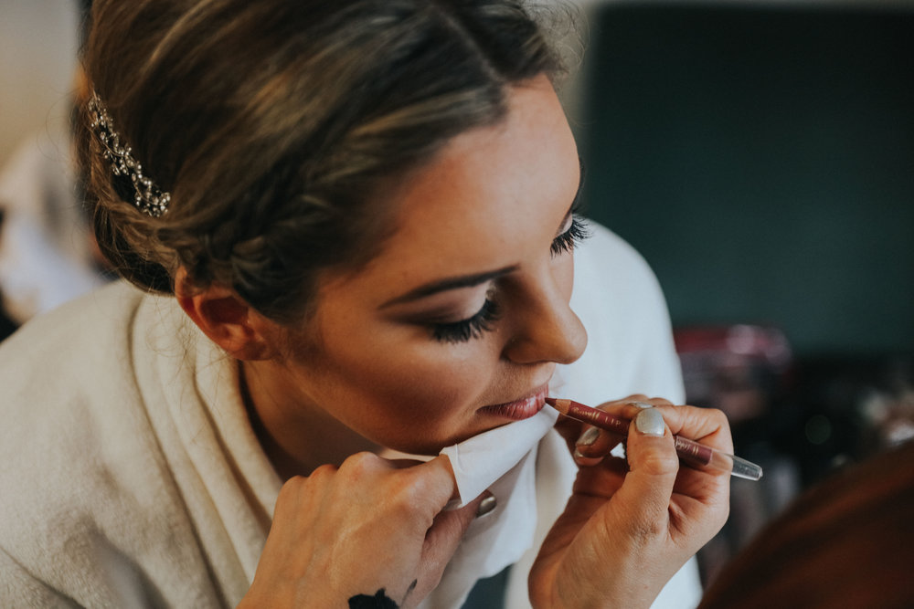 bride having lip liner applied