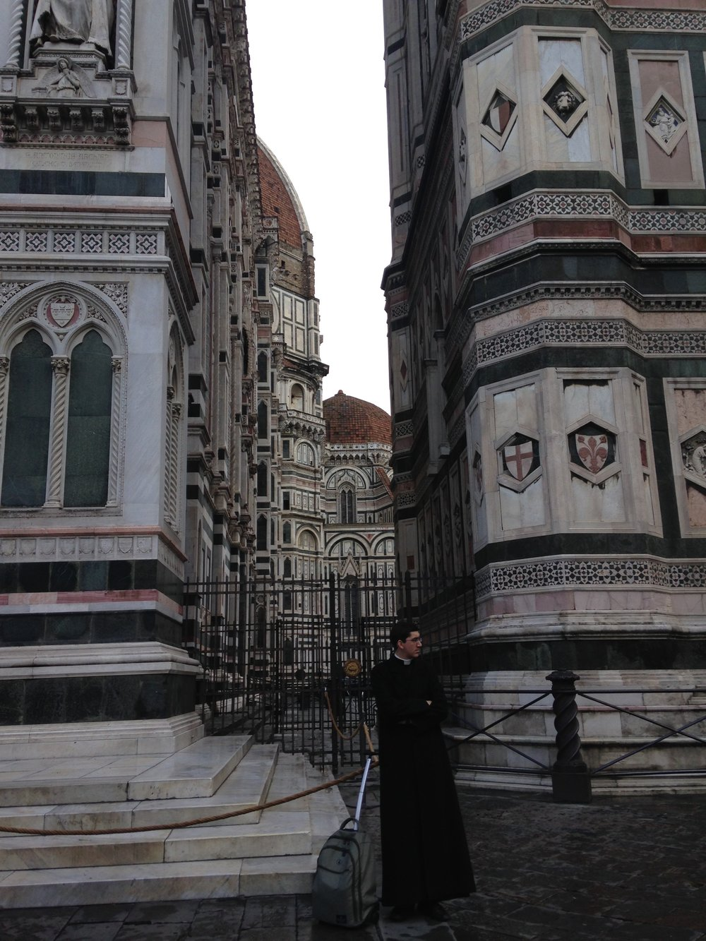 A priest waiting in front of the Florence Cathedral
