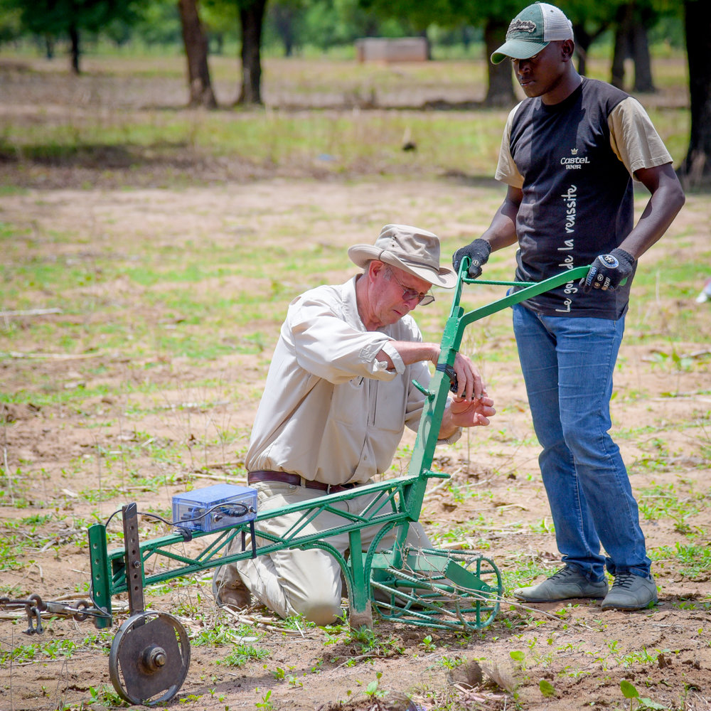 A partnering professor from Michigan State University with a graduate student from Polytechnic University of Bobo-Dioulasso field testing a rippling plow in the West African country of Burkina Faso.