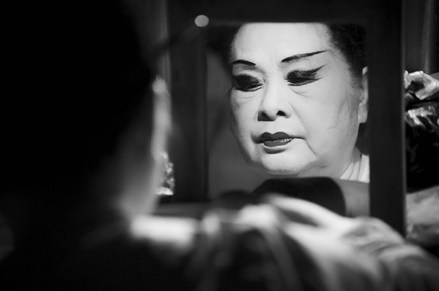 Chinese Opera performer applying makeup