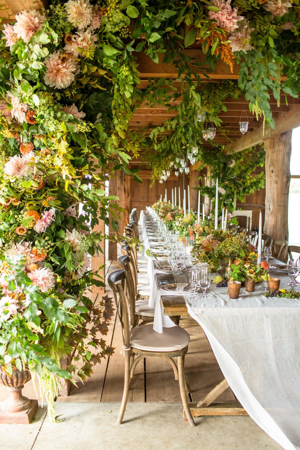 a long wedding table under a floral pergola in fall with fall colors
